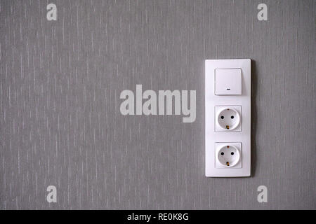 Two power sockets and Light switch on gray wall. Close-up. - Stock Photo