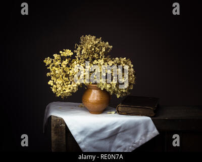 Dramatic chiaroscuro style photo of dried hydrangea flowers with old book on dark background. Melancholy still life with copy space. - Stock Photo