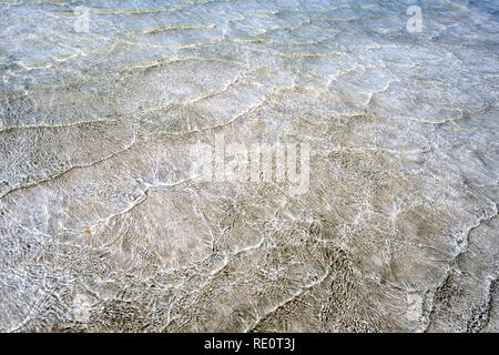 Empty background with natural textured pattern created by small sea waves in shallow waters of golden sand beach. Water surface is shining because of  - Stock Photo