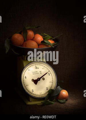 Oranges, tangerines on scales on rustic hessian. Dark, chiaroscuro style still life. Vintage theme. Vertical shot. - Stock Photo