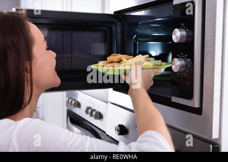 Close-up Of A Young Woman Heating Fried Food In Microwave Oven - Stock Photo