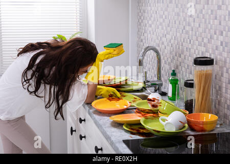 Side View Of Tired Young Woman Leaning Near Sink With Dirty Utensils In Kitchen - Stock Photo