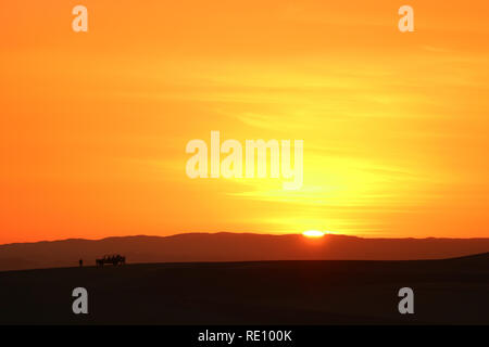 Incredible sunset over the sand dunes of Huacachina desert with the silhouette of tourists dune buggy, Ica region, Peru - Stock Photo