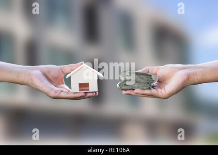 Home loan, mortgages, debt, home buying concept. Hand holding small resident exchange money on blurred real estate background. Exchange of finances an