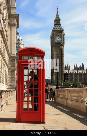 A man using the phone in a typical British telephone box on the sidewalk with the famous Elizabeth Tower (Big Ben) in the background - London, UK - Stock Photo