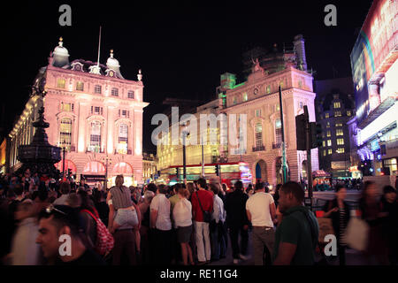 Crowd of people standing around the Shaftesbury Memorial Fountain at Piccadilly Circus in London, United Kingdom - Stock Photo