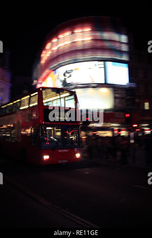 Typical red double-decker bus rushing across Piccadilly Circus in London, United Kingdom - Stock Photo