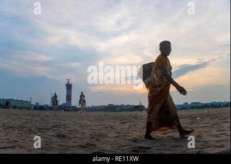 An Indian woman on Marina Beach near Chennai in southern India, enjoying the Bay of Bengal sea - Stock Photo