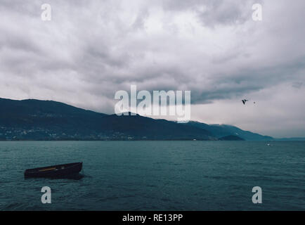Lonely wooden boat in Ohrid Lake on a cloudy day - Stock Photo