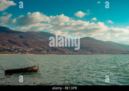 Lonely wooden boat in Ohrid Lake on a sunny day - Stock Photo