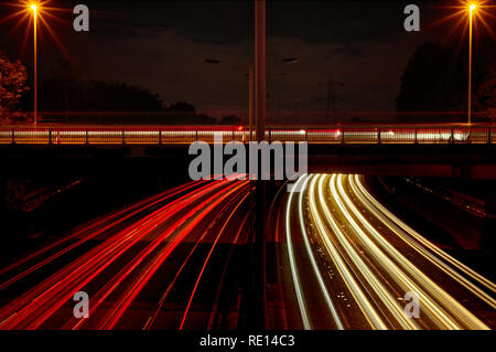 Red and white vehicle light trails as UK motorway traffic passes a bridge in both directions, trails from more vehicles are seen on the bridge. - Stock Photo
