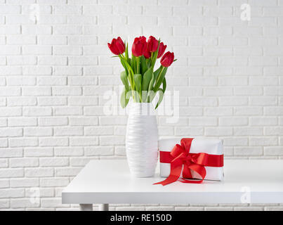 Red tulips in white vase next to a gift box with red ribbon - Stock Photo