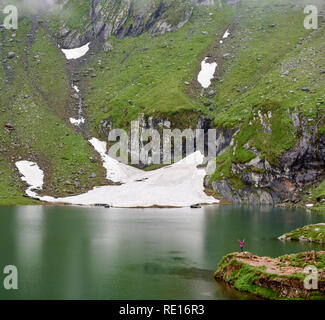 People and nature. Small figure of woman compared to greatness of nature. Green rocks and meadows near Vidraru lake in Romania. Amazing view scenery hands up female snow mountain beautiful landscape - Stock Photo