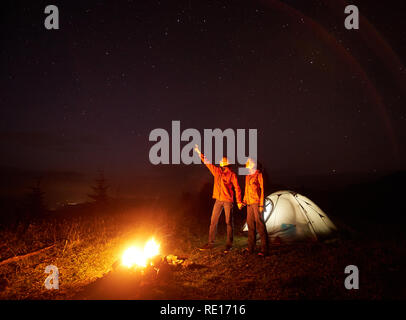 Camping night in mountains. Young couple standing in front of illuminated tent, holding hands lit by burning bonfire, boy points at beautiful starry sky to girl. Tourism and beauty of nature concept. - Stock Photo