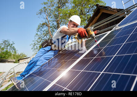 Technician installing solar photo voltaic panel to metal platform using screwdriver on bright blue sky background. Stand-alone solar panel system installation concept. - Stock Photo