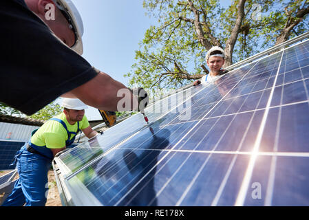 Team of three technicians working on exterior voltaic solar panel system installation in rural countryside on bright sunny summer day. Renewable ecological cheap green energy production concept. - Stock Photo
