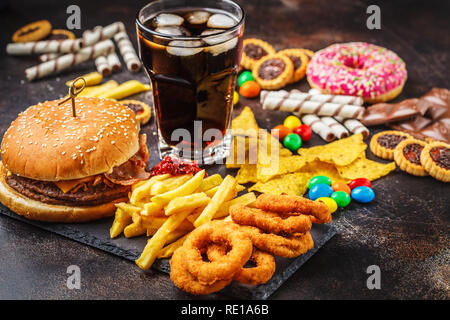 Junk food concept. Unhealthy food background. Fast food and sugar. Burger, sweets, chips, chocolate, donuts, soda on a dark background. - Stock Photo