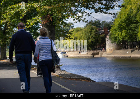 Man and woman walking down a path next to the River Ouse in York,North Yorkshire,England,UK. - Stock Photo