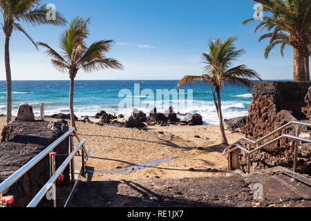 Puerto del Carmen beach in Lanzarote, Canary islands, Spain. blue sea, palm trees, selective focus