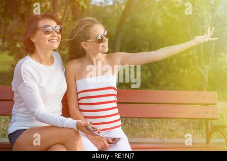 Communication between parent and child. Mom and daughter teenager talking and laughing while sitting on the bench in the park - Stock Photo