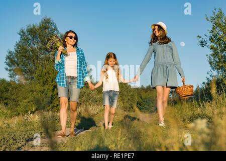 Happy mother and two daughters holding hands walking along rural country road with wildflowers, basket of berries. Sunny summer day, sunset. - Stock Photo