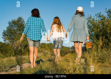 Happy mother and two daughters holding hands walking along rural country road with wildflowers, basket of berries. Sunny summer day, sunset, back view - Stock Photo