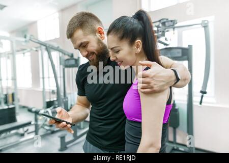 Young woman talking with personal trainer in gym, looking in smartphone and discussing. Fitness, sport, training, people, healthy lifestyle concept. - Stock Photo