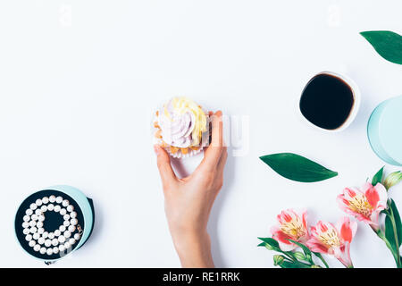 Flat lay composition woman's hand holding cupcake with cream on white table next to pearl necklace in box, cup of coffee and flowers, top view. - Stock Photo