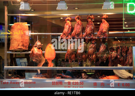 Roasted ducks, giant squid and other delicious Chinese food hanging in a store window in China Town in London, United Kingdom - Stock Photo