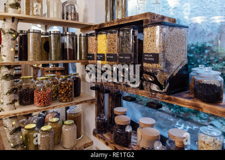 Organic shop interior. Display of glass jars on shelves filled with fresh and dry produce in grocery store. - Stock Photo