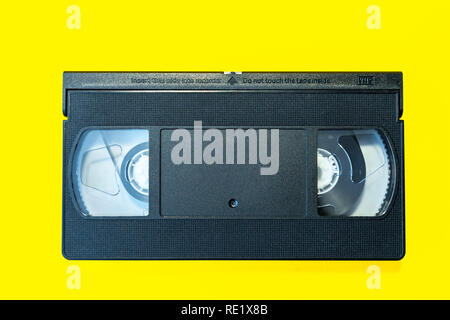 VHS Cassette on a yellow background. Recording tape. - Stock Photo