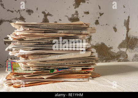 A stack of old newspapers on a table and a wall in a bad state of background - Stock Photo