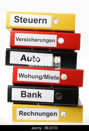 Black, yellow and red ring binders, labelled in German for taxes, insurance, car, apartment, rent, bank accounts, invoices - Stock Photo