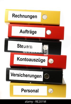 Black, yellow and red ring binders, labelled in German for invoices, contracts, taxes, bank statements, insurance and personal - Stock Photo