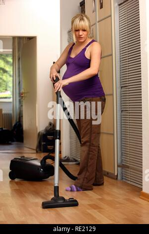Pregnant woman, 9th month, at home, doing light housework, vacuuming - Stock Photo