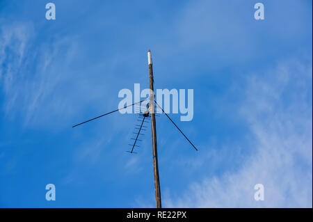 TV antenna attached to a wooden pole against the blue sky - Stock Photo