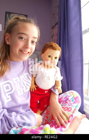 This images includes on original Tiny Tears doll which has been handed down from the young girls grandmother to her. The doll is original piece. - Stock Photo
