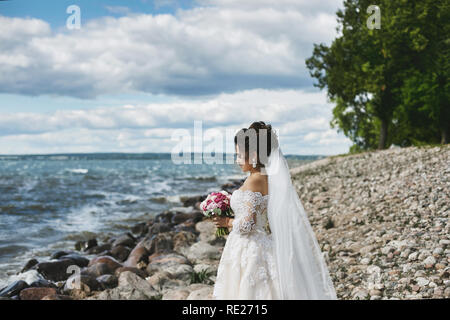 Elegant and fashionable brunette plus-size model girl in the stylish lace wedding dress with stylish hairstyle and with the bouquet of flowers in her hands stands at the sea coast - Stock Photo