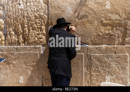 An Ultra-Orthodox Jew prays at the Western Wall in Jerusalem - Stock Photo