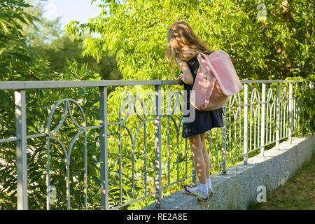 Girl schoolgirl blonde with backpack in school uniform near fence in the school yard, back to school. - Stock Photo
