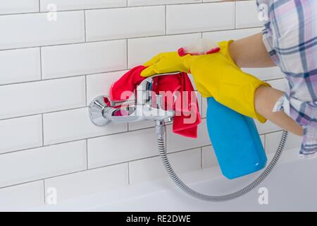Housework and domestic lifestyle. Woman doing chores in bathroom at home, cleaning wash basin and tap with spray detergent. - Stock Photo