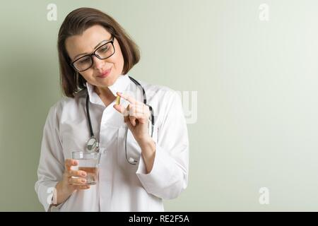 Female doctor takes vitamin capsule. Healthy lifestyle, nutritional supplements, vitamin d, e, fish oil capsules. Copy space - Stock Photo