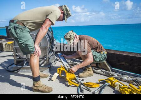 Chief Petty Officer Jesse Hamblin, right, and Petty Officer 1st Class Christopher Chilton, both assigned to Underwater Construction Team (UCT) 2's Construction Dive Detachment Bravo (CDDB), replace the chain on a hydraulic chainsaw in Diego Garcia, British Indian Ocean Territory,  Nov. 8, 2016.  CDDB is performing precision underwater demolition and light salvage to remove obstructions from Diego Garcia's deep draft wharf. CDDB is on the third stop of their deployment, where they are conducting inspection, maintenance, and repair of various underwater and waterfront facilities while under Comm - Stock Photo