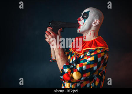 Mad bloody clown with a gun in his mouth, circus horror. Man with makeup in carnival costume, crazy maniac - Stock Photo