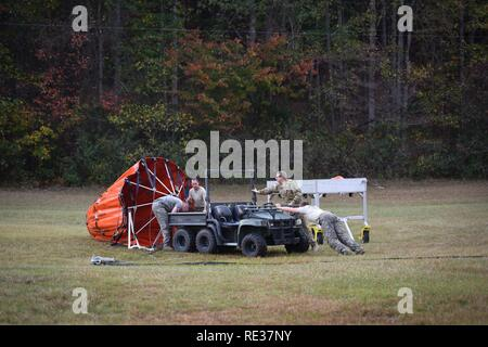 U.S. Army Warrant Officers Mark Melikant and James Pressley, Sgt. Ira Duville, Sgt. Timothy Pinelli, and Spc. Charles Coleman, Jr., Detachment 1, Company B, 2-238th General Support Aviation Battalion, South Carolina Army National Guard, disassemble and pack a Bambi-bucket system for a CH-47F Chinook heavy-lift cargo helicopter in Greenville, South Carolina, Nov. 10, 2016. The crew and the aircraft have been tasked to support the South Carolina Forestry Commission in containing a remote fire near the top of Pinnacle Mountain in Pickens County, South Carolina. - Stock Photo