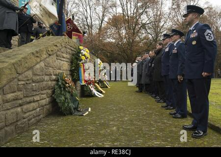 Leaders from the 52nd Fighter Wing, Spangdahlem Air Base, Germany, and German citizens pause after presenting wreaths during a German National Day of Mourning observance ceremony at the Kolmeshöhe Military Cemetery in Bitburg, Germany, Nov. 13, 2016. The day, known as Volkstrauertag in German, observes the human cost of war and was established following the conclusion of the First World War. - Stock Photo