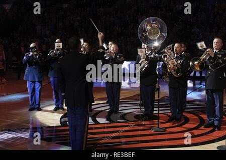 Chief Warrant Officer 4, Russell Houser, band director of the 56th Army Band, leads the playing of the national anthem on Veterans Day Nov. 11, 2016, in Portland, Ore. - Stock Photo