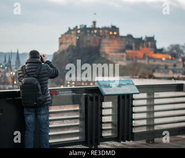 A photographer (foreground) taking a picture of Edinburgh's Castle from a roof top terrace. Travel photography. Tourism - Stock Photo