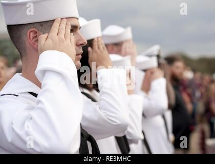 (COLLEGE STATION, Texas) Petty Officer 2nd Class Andrew Tonski, Junior Sailor of the Year for the aircraft carrier USS George H.W. Bush (CVN 77), salutes during a performance of the national anthem at an pass and review of ROTC cadets at Texas A&M University. The pass and review is part of a two-day namesake trip to Texas where Sailors engaged with the local community about the importance of the Navy. Stock Photo