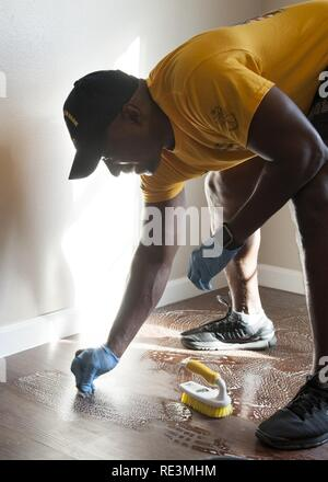 (COLLEGE STATION, Texas) USS George H.W. Bush (CVN 77) Command Master Chief Huben Phillips cleans the floor of a future home during a Habitat for Humanity project in College Station, Texas. The project is part of a two-day namesake trip to Texas where Sailors engaged with the local community about the importance of the Navy. Stock Photo